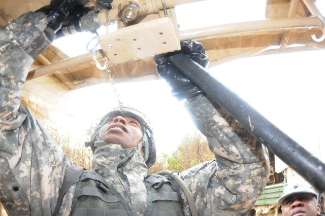 Spc. Gary Jones works on a one of the 12 shower heads that make up a mobile shower facility.