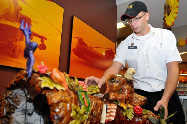 Spc. Steven Haney, a cook at Fort Riley's Demon Diner, arranges a Thanksgiving cornucopia the night before the dining facility's holiday meal service.