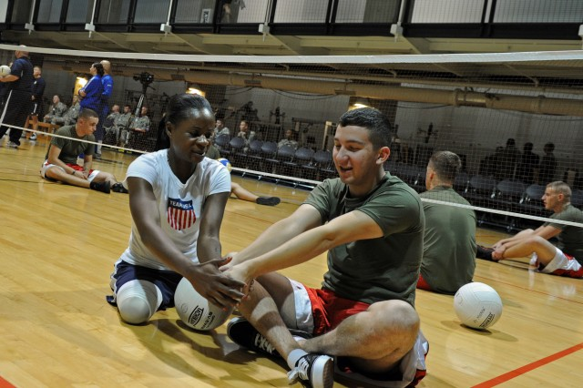 Former Army Sgt. Kari L. Miller, who lost her legs to a drunk driver in 1999, instructs a Marine on how to hold his hands for a volleyball serve. The Army Warrior Transition Command sponsored a multiservice sitting volleyball tournament at the Pentagon Athletic Center Nov. 22, 2011.