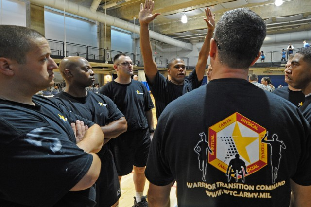 "Sgt. Juan Alcivar reminds the Army team when they're on the front line at the net to keep their hands high on the serve and one ""cheek"" on the court during the sitting volleyball tournament at the Pentagon Nov. 22, 2011."
