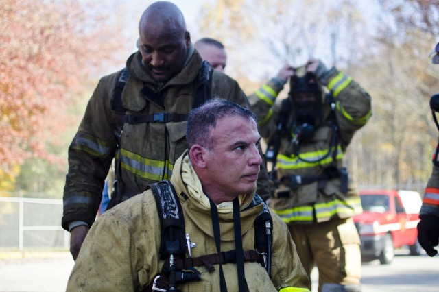 Garrison Commander Col. Edward C. Rothstein rests after participating in a firefighter training exercise with other garrison leaders at the Anne Arundel County Fire Department Training Academy in Millersville on Nov. 7.