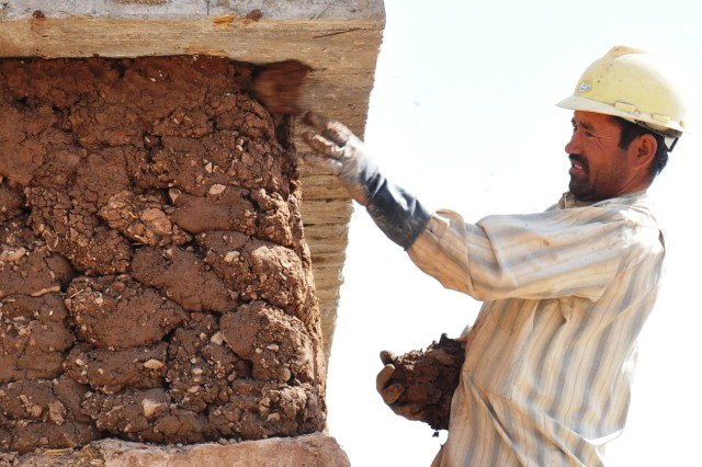 An Afghan employee flings clay/mud to finish the outer wall of an Adobe-style constructed building at the 4th Zone Afghan Border Patrol compound Sept. 27, 2011, in western Afghanistan.