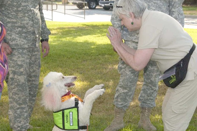 Divine Canine therapy dog, Annie, responds to the commands of her owner, Pam Baggett. Divine Canines is an Austin-based nonprofit dog therapy group. Volunteers visit Warrior Transition Brigade Soldiers monthly as guests of WTB's occupational therapy program. Watching Annie perform are WTB Soldiers, Sgt. Alex Hammell and Pvt. 1st Class Michael Aiken.