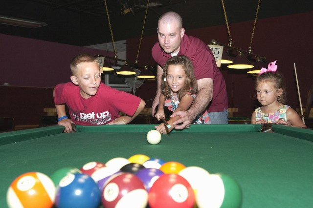 While Capt. Malcolm Wilson, commander, Company B, 1st Battalion, Fort Hood Warrior Transition Brigade, helps his daughter, Emma, take a crack at billiards, her brother, Jack, and sister, Ellie, watch. WTB Family Readiness Group coordinators plan quarterly events for Soldiers and their families in various ways, such as chili cook-offs, picnics and off-post events such as Family Pool Day. According to Wilson, the events not only promote bonding and family socialization, but also build morale because it gets Soldiers off the installation.