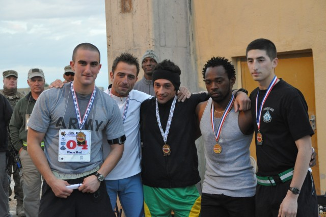 The male winners of the Forward Operating Base Farah Thanksgiving Turkey Trot were recognized with metals for their performance in the race.  The five kilometer race began a day of Thanksgiving festivities at the FOB.  From left to right Eric LaDaw fifth place, Gigi Vincbrico fourth place, Chico Ciro third place, Eric Irungu first place, Anthony Thompson second place.