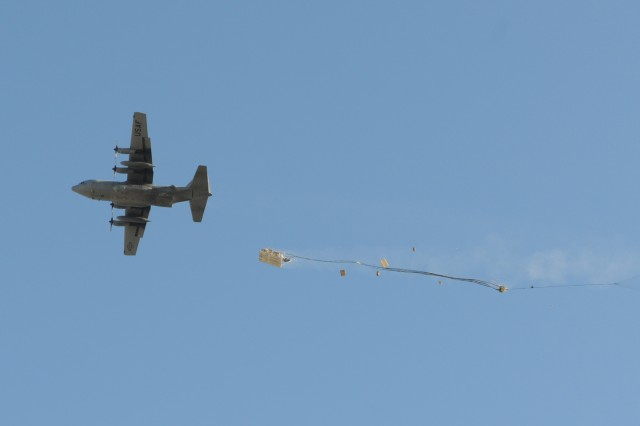 A crew pushes a platform carrying a 4k forklift out of a C-130 aircraft Nov. 23, 2011, over a drop zone near Forward Operating Base Curry in Eastern Afghanistan. It was the first forklift ever dropped in theater and weighing 15,000 pounds, it was also the heaviest platform ever dropped in theater as well.