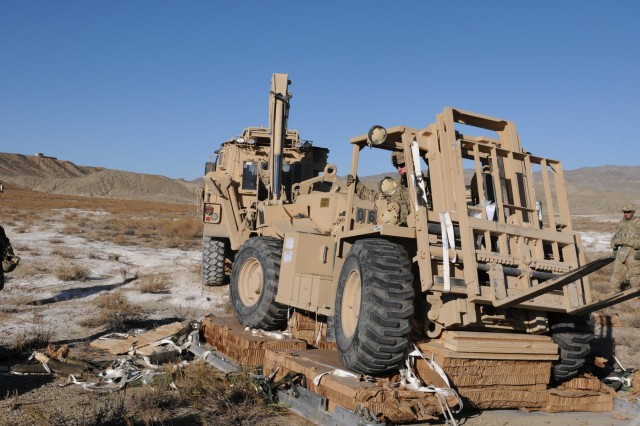 Soldiers from B Company, 9th Engineer Battalion, recover a 4k forklift Nov. 23, 2011, from the platform it arrived on at a drop zone near Forward Operating Base Curry in Eastern Afghanistan. It was the first forklift ever dropped in theater and weighing 15,000 pounds, it was also the heaviest platform ever dropped in theater as well.