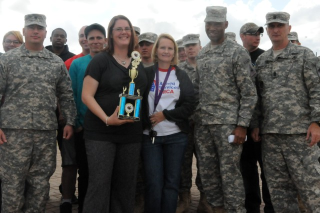 Nina Carey, coordinator for the Armed Services YMCA Junior Enlisted Family Center, Maj. Gen. Dana J.H. Pittard, Commanding General, 1st Armored Division and Fort Bliss, and Command Sgt. Maj. David S. Davenport Sr., Command Sergeant Major, 1st Armored Division and Fort Bliss present the first place trophy to Soldiers and family members who helped with 1st Brigade, 1st Armor Division's wooden replica Stryker during the annual Team Bliss Thanksgiving food basket drive Nov. 21 at Soto Physical Fitness Center.
