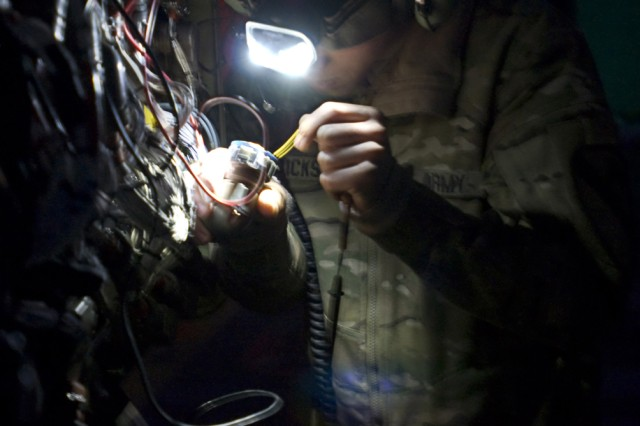 CAMP MARMAL, Afghanistan -- Spc. Andrew Glickstein, an armament technician assigned to TF Lobos, 1st Air Cavalry Brigade, 1st Cavalry Division, originally from San Antonio, Texas, checks for continuity as he troubleshoots wires that are part of the weapons system of an AH-64D Apache helicopter Nov. 27. (U.S. Army photo by Sgt. Felix Acevedo)