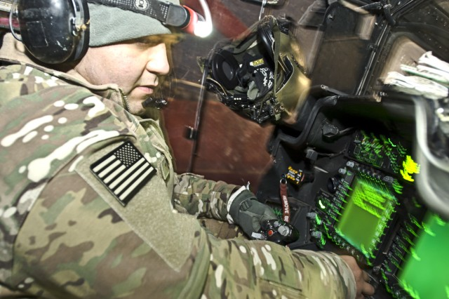 CAMP MARMAL, Afghanistan -- Sgt. Ben Davila, the armament maintenance noncommissioned officer in charge for Company D, Task Force Lobos, 1st Air Cavalry Brigade, 1st Cavalry Division, originally from Corpus Christi, Texas, works from the cockpit of an AH-64D Apache helicopter as he troubleshoots a fault pertaining to the aircraft's weapons system Nov. 27. (U.S. Army photo by Sgt. Felix Acevedo)