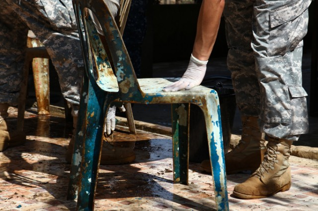 Soldiers from Eighth Army's 65th Medical Brigade clean debris from chairs at the Sanamchai School in Lopburi, Thailand.