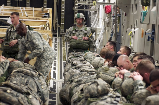 Lt. Col. David Gardner, commander of 2nd Battalion, 505th Parachute Infantry Regiment, 3rd Brigade Combat Team, 82nd Airborne Division ,surveys the Paratroopers recently rigged and ready to jump following an in-flight rigging exercise aboard an Air Force C-17 Globemaster flying over a sleeping North Carolina, Nov. 23, 2011. The exercise was designed to give jumpmasters a chance to become familiar with the challenges of rigging paratrooper safely while in the air.
