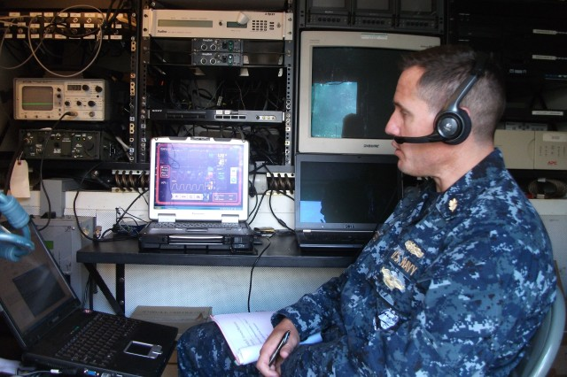 Cmdr. Raymond Cestero, U.S. Navy surgeon, reviews incoming combat casualty telemetry data from TEMPUS-Pro and provides telementoring to combat medics on the scene.