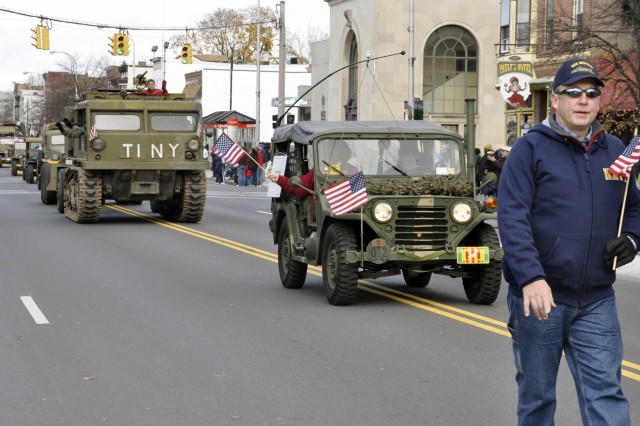 Arsenal Public Works Supervisor Tom Herold marches in front of military vehicles supplied to the Arsenal by the Hudson-Mohawk Military Vehicle Collectors Club.