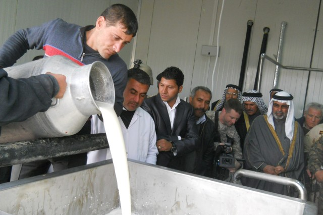 Workers from Iraq's Zaidon milk processing facility pour a fresh batch of raw milk out into a filtering tank, Jan. 20, demonstrating the first step in its transition to a packaged, marketable product during a tour.