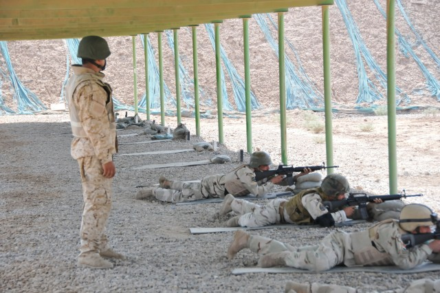 Iraqi Sgt. Mustafa watches as instructors from the Camp Taji Noncommissioned Officer Academy fire while qualifying with M-16 Rifles. U.S. trainers worked to build the skills and confidence of the cadre of the academy by making them experts on both the M-16 and AK-47 rifles.