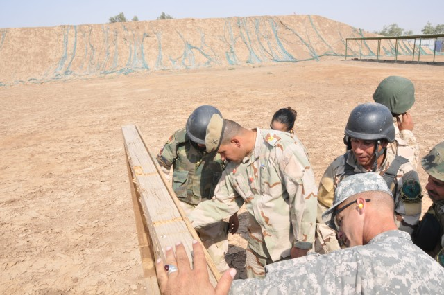 Iraqi soldiers at the Camp Taji NCO Academy check their targets after qualification firing. The confidence that the Iraqi NCOs gain from attending the academy has encouraged Iraqi commanders to send more of their NCOs to the offered courses.