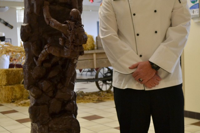 Sgt. Ryan Woolman, a food specialist in 10th Brigade Support Battalion, 1st Brigade Combat Team, stands next to his statue made of a chocolate-based compound at the Riva Ridge Dining Facility on Nov. 22. The statue is a representation of the Military Mountaineers Monument in Memorial Park.