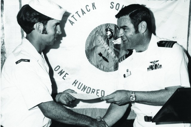 Alan K. Peterson (left) accepts the Plane Captain of the Month Award from his squadron commander on the USS Kitty Hawk in 1972. Peterson served in the Lemoore, Calif.-based Attack Squadron 195 during his time in the U.S. Navy. He is the last Vietnam veteran to serve in the North Dakota National Guard and retired Nov. 30, 2011.
