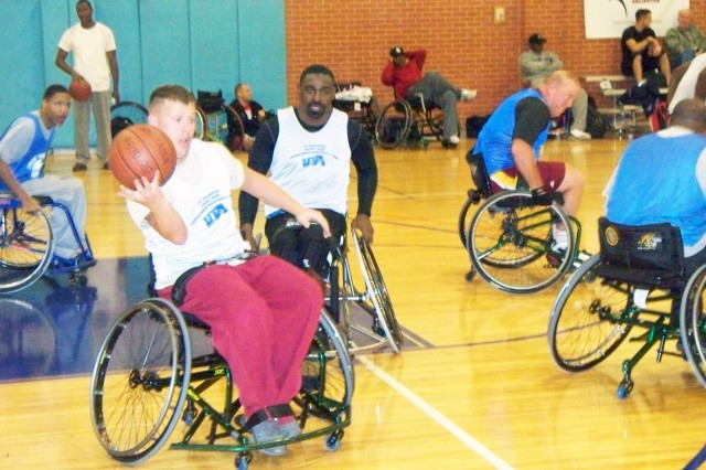 Spc. Jared Page, 1st Battalion, 158th Field Artillery, grabs a pass while rolling down the court at a wheelchair basketball clinic at the University of Texas at Arlington. He was trying out for a spot on the All-Army team that will compete in the Warrior Games.