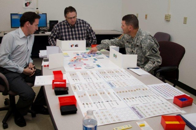 Wraparound: Lt. Col. James Miller (right) a senior military analyst from Training and Doctrine Command's office at Fort Lee, James Nutwell (center), a social scientist for the complex operations data development activity, and Phil Haussmann (left) from CNA Analysis and Solutions assigned to TRAC Methods and Research Office play a tabletop portion of the Irregular Warfare Tactical War Game. This portion of the game is used to represent the Army players higher headquarters and generates larger operations, activities, and scenarios within the game world. Eventually it's expected that this portion of the game will be converted into a computer simulation as well.