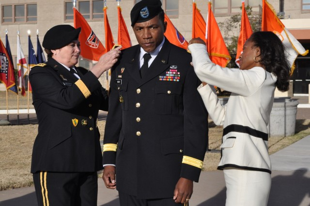 Lt. Gen. Susan S. Lawrence, the Army's Chief Information Officer/G-6 and former commanding general of NETCOM, and Latonya Henry, wife of Brig. Gen. Frederick Henry, NETCOM deputy commander, place his new rank on his shoulders.