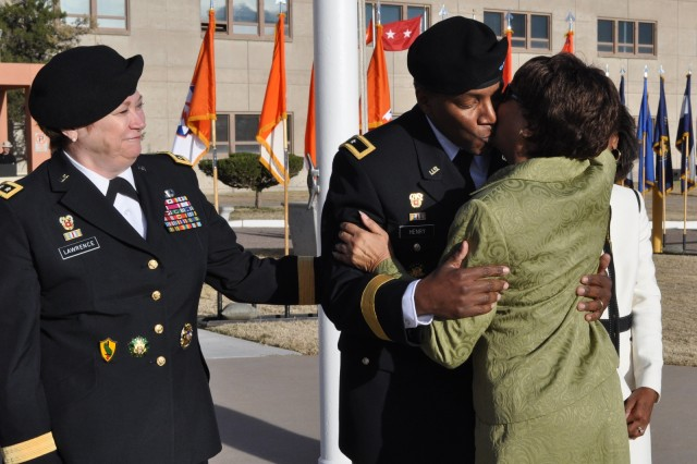 Brig. Gen. Frederick Henry, NETCOM deputy commander, receives a hug from his mother, Faith Henry, after giving him his new beret. Lt. Gen. Susan S. Lawrence, the Army's Chief Information Officer/G-6 and former commanding general of NETCOM, looks on.