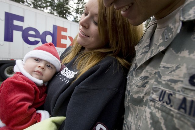 "Airman 1st Class Arnold Palmer III, his wife Amanda and three-month-old son, Arnold Palmer IV, were selected to receive a Christmas tree during the 5th annual ""Trees for Troops,"" program on JBLM.  Since 2005, the Christmas SPIRIT foundation's ""Trees For Troops""  donated by tree growers throughout the United States has delivered approximately 17,000 trees each year to 60+ military bases throughout the U.S. and overseas.  This year more than 600 trees were delivered to JBLM."