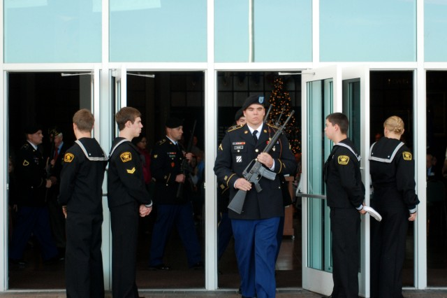 Pvt. Matthew W. Cline, an aviation operations specialist with Headquarters and Headquarters Company, 2nd Battalion, 3rd Aviation Regiment, leads the Knighthawk firing squad into position during the Pearl Harbor Remembrance Day ceremony Dec. 4, 2011, at the Mighty Eighth Air Force Museum of Pooler, Ga. Nine 3rd Combat Aviation Brigade Soldiers fired a 21-gun salute to honor the fallen American defenders.