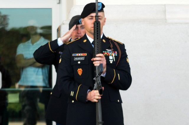 """Spc. Vincent Holsather, a Chinook repair technician with Delta Company, 2nd Battalion, 3rd Aviation Regiment, salutes during the playing of """"Taps"""" at the Pearl Harbor Remembrance Day ceremony Dec. 4, 2011, at the Mighty Eighth Air Force Museum of Pooler, Ga. Holsather was one of nine 3rd Combat Aviation Brigade Soldiers who acted as firing squad to honor the fallen American defenders."""