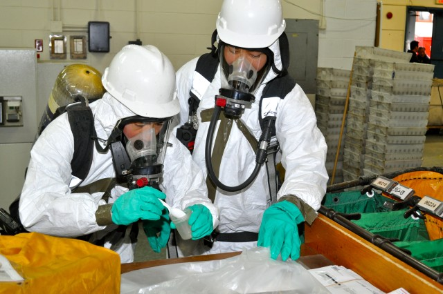 The Fire Department entry team takes samples from a letter suspected of containing hazardous materials during a Suspicious Package Training Exercise conducted in the Main Post Mail Room, Nov. 30. (Photo by Cpl. Sung Il Choi)