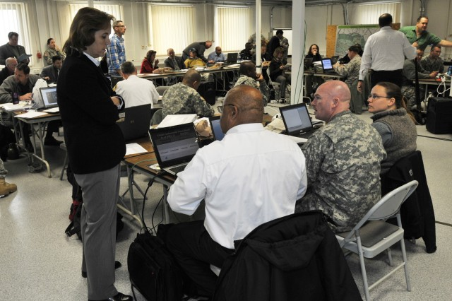 Mary Cooper, Chief, Grafenwoehr Garrison Human Resource Division, consults with her team during the annual U.S. Army Garrison Grafenwoehr's force protection exercise, which took place for the first time in its history in a virtual world. The all-day event held Dec. 2, 2011 at the Joint Multinational Training Command's Simulation Center took place in a digital replica of the USAG Grafenwoehr Main post. The exercise is implemented once a year to test the reactions and responses of first-responders, as well as the local garrison command structure. (U.S. Army Photo by Michael Beaton)