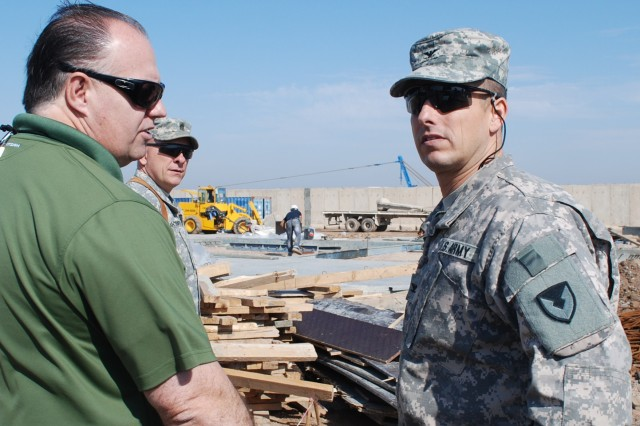 Col. John S. Laskodi, commander 402nd Army Field Support Brigade, discusses progress on the construction of a mine resistant, ambush-protected vehicle maintenance facility at Basrah, Iraq, with Dannia Buster, contract officer representative. The operation supports the Department of State as part of the transition in Iraq.