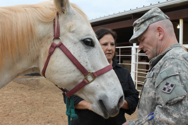 Jan Smith, Spirithorse Chisholm Trail Center owner, talks with Sgt. Paul Hill about a problem that one of her therapy horses is having with his hoof.