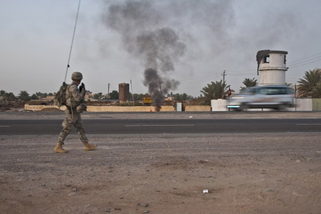 A plume of black smoke builds in the distance and cars speed by as Sgt. Michael Drake, a military policemen assigned to Headquarters Company, 2nd Brigade Special Troops Battalion, 82nd Airborne Division, walks along a road outside Camp Taji, Iraq, during a dismounted patrol Dec. 2, 2011.