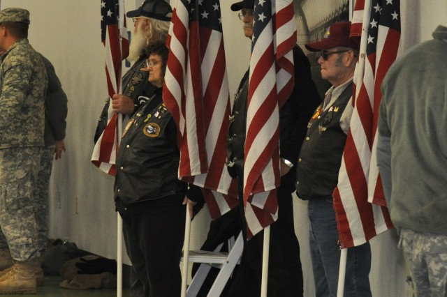 """FORT LEONARD WOOD, Mo. """" Local Patriot Guard Riders stand behind family members and friends during a deployment ceremony Dec. 5 at Nutter Field House. Patriot Guard Riders is an organization that provides support for troops by attending, by invitation, any military ceremony."""