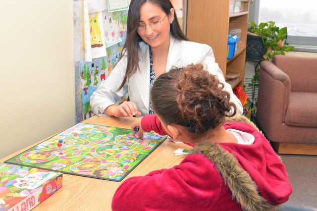 Mariella Reano, licensed clinical social worker at CRDAMC's Child and Adolescence Psychiatric Evaluation Service (CAPES), plays a game with one of her young patients to help encourage positive behaviors in a recent therapy session. (U.S. Army photo by Patricia Deal, CRDAMC Public Affairs)