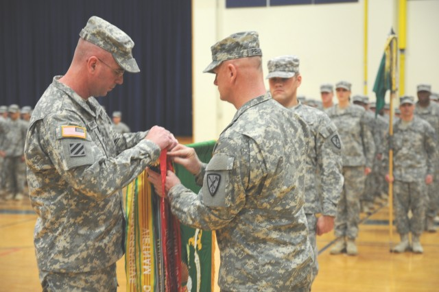 Lt. Col. Carl L. Parsons, commander, 504th Military Police Battalion and Command Sgt. Maj. Ted L. Pearson, acting command sergeant major, 504th Military Police Battalion, affix their Meritorious Unit Award streamer to their unit colors. The 504th MP Battalion earned the award during their recent deployment to Afghanistan.