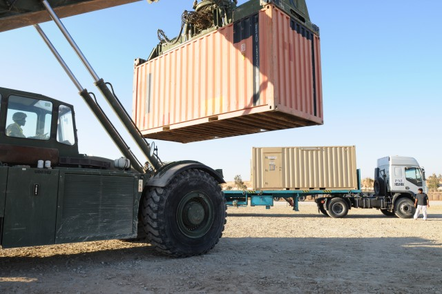 Sgt. Rayon Cunningham, a team leader with 407th Brigade Support Battalion, 2nd Brigade, 82nd Airborne Division, loads a shipping container onto a flatbed truck on Al-Asad Air Base, Iraq, on Dec. 3 to be sent to Kuwait. Paratroopers assigned to 407th BSB are among the last service members on Al-Asad and are preparing to turn the base over to the Iraqi Army as U.S. Forces withdraw from Iraq by the end of the month. Cunningham is a native of Spicy Hill Trelawny, Jamaica.