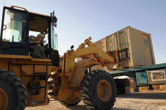 Spc. Gabriel Ramirez, an ammunition specialist assigned to A Co., 407th Brigade Support Battalion, 2nd Brigade, 82nd Airborne Division, loads a shipping container onto a flatbed truck headed to Kuwait on Al-Asad Air Base, Iraq, Dec 3. Paratroopers with 407th BSB are moving critical equipment out of Iraq days before the turnover of the camp to the Iraqi Army. Ramirez is a native of San Diego, Calif.