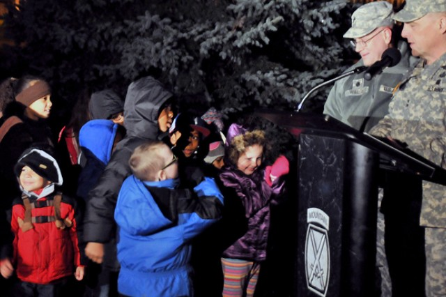 Maj. Gen. Mark A. Milley, Fort Drum and 10th Mountain Division (LI) commander, invites children to join him at the front of the crowd Thursday during Fort Drum's annual lighting of the Christmas tree and menorah.