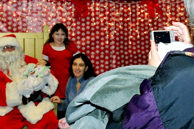 Nancy Velasco, wife of Sgt. William Velasco, a scout recently deployed to Afghanistan with 3rd Squadron, 71st Cavalry Regiment, poses with her daughter, Xena, and newborn, Samanntha, while her mother, Linda Parra, snaps a picture Thursday at a holiday celebration in Fort Drum's Youth Center.