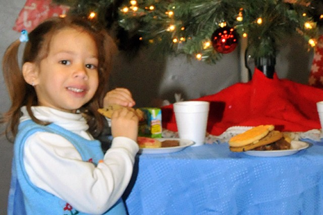Sofia Perez, 4, daughter of Staff Sgt. Jose Perez, physical therapist at Fort Drum MEDDAC, eats a holiday treat during Fort Drum's annual tree and menorah lighting.