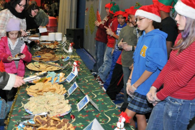 Youths with Fort Drum's Child, Youth and School Services dressed at elves Thursday to assist with setting up holiday treats for revelers.