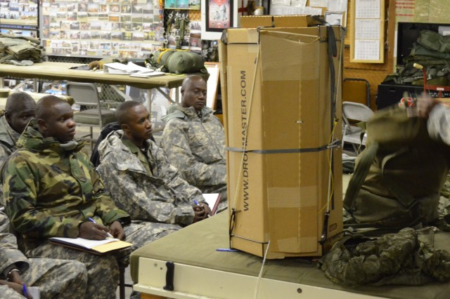 Sgt. 1st Class Hershel Gillins, with the 21st Theatre Sustainment Command (Germany), instructs soldiers from Mali Africa how to assemble and disassemble different containers for aerial resupply missions, Nov. 19, 2011, at Camp Dawson, Kingwood, W.V. Malian Defense Forces train on delivery systems that can be dropped into an area in natural disaster situations.