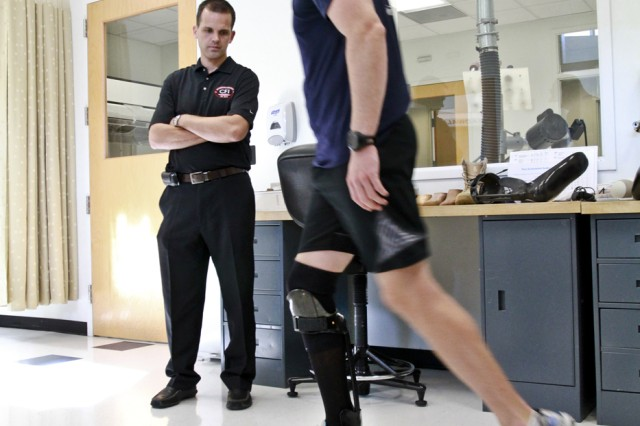 1st Lt. Matthew Anderson, an infantry platoon leader with an injured lower leg, tries out the fit of an adjusted Intrepid Dynamic Exoskeletal Orthosis brace as Ryan Blanck, the brace's creator, watches him walk at the Center for the Intrepid in San Antonio, Nov. 10, 2011. Anderson returned to the center to have one brace adjusted and get fitted for another.