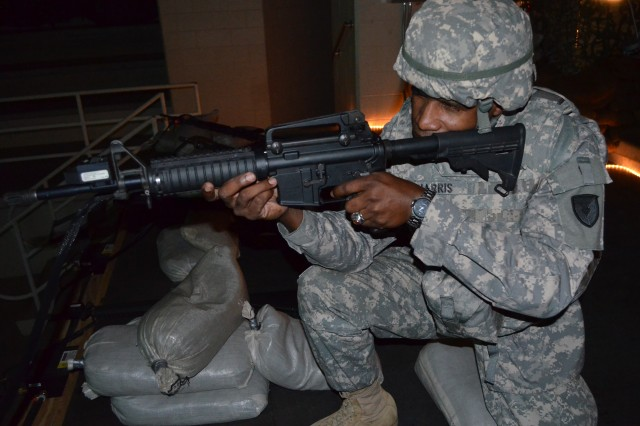 "Sgt. 1st Class Lascelles Cuff, G3 training NCO, demonstrates how to evaluate a casualty using the ""look, listen, feel"" technique during the Expeditionary Contracting Command headquarter's warrior training."
