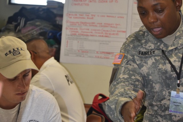 U.S. Army Kwajalein Atoll Fire Department Captain Scott Thomas listens as Master Sgt. Michelle Fairley discusses a case study involving a hazardous materials spill. Fairley accompanied instructor Dennis Goudy to teach emergency management classes on Kwajalein.