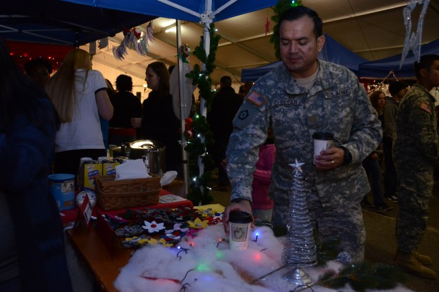 Maj. Shane Cuellar, 16th Sustainment Brigade, gets a warmer drink at the 16th Special Troops Battalion stand during the Christmas market Dec. 1. The booth offered miniature decorated Christmas trees and Hooah flowers, which are meant to be worn to show pride for a unit.