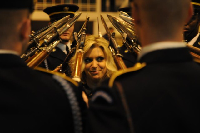 "Anna Wiliamson of ITV's Daybreak standsmotionless as the U.S. Army Drill Team points their Bayonets towards her head while performing what is called ""Hat Band"" during rehearsals at Earl's Court, London Dec. 1, 2011."